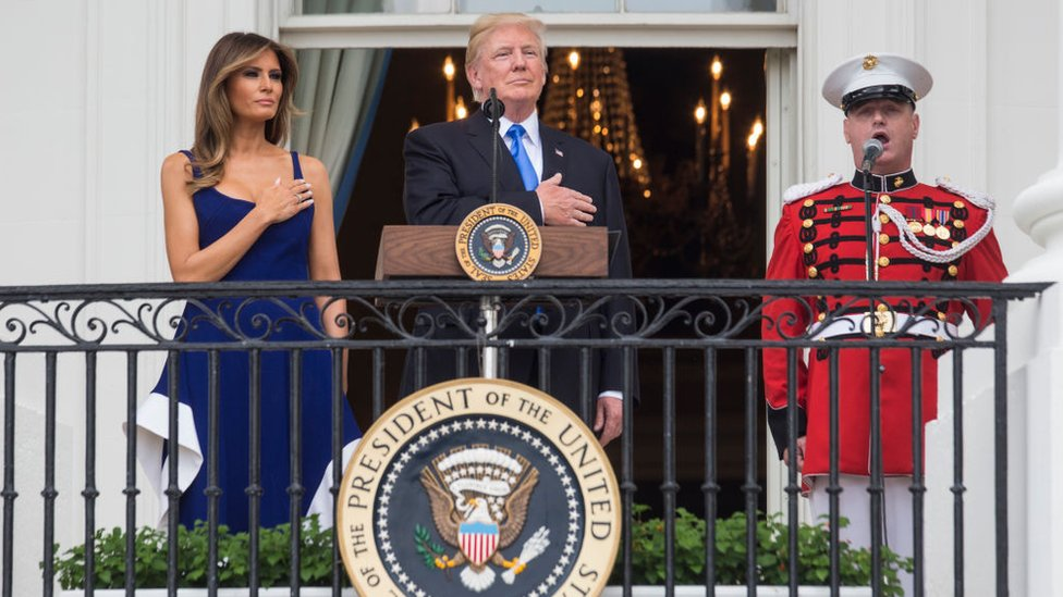 US President Donald Trump and first lady Melania Trump observe the playing of the national anthem from the Truman Balcony on July 4, 2017 in Washington, DC
