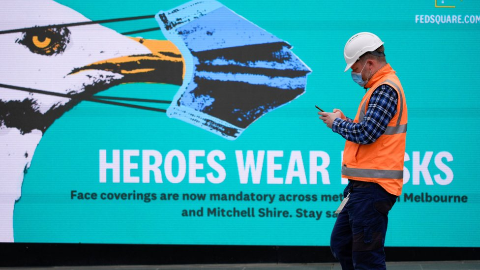 Un hombre frente a un cartel en Melbourne
