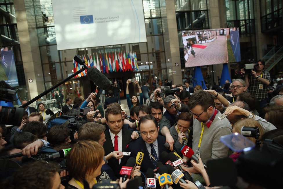 Journalists scramble to speak to a Polish minister at the European summit