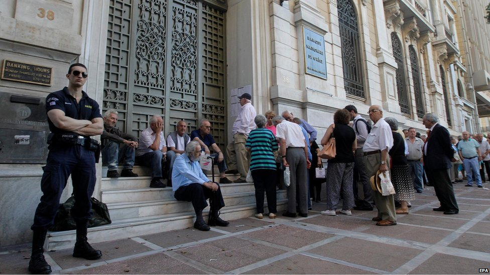 A policeman stands guard as Greek pensioners line up to get part of their pensions in front of a branch of National Bank of Greece in Athens, Greece (9 July 2015)