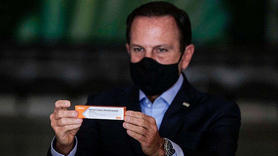 Foto de João Dória, governador de São Paulo, segurando embalagem da CoronaVac