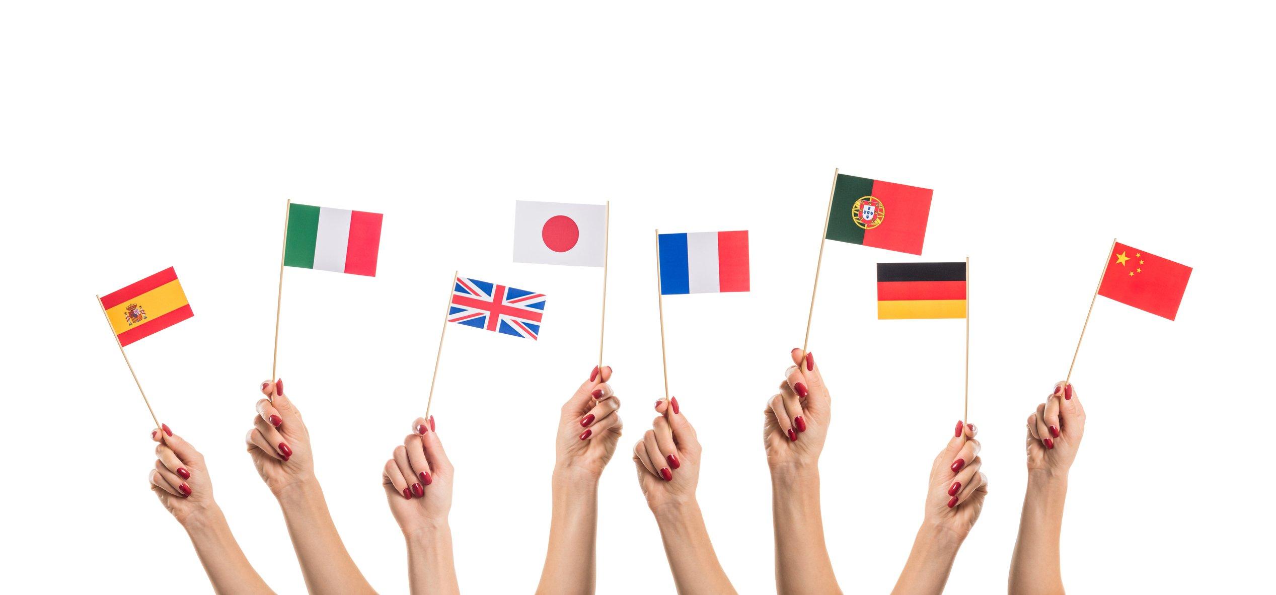 Manos de mujer sosteniendo banderas de distintos países