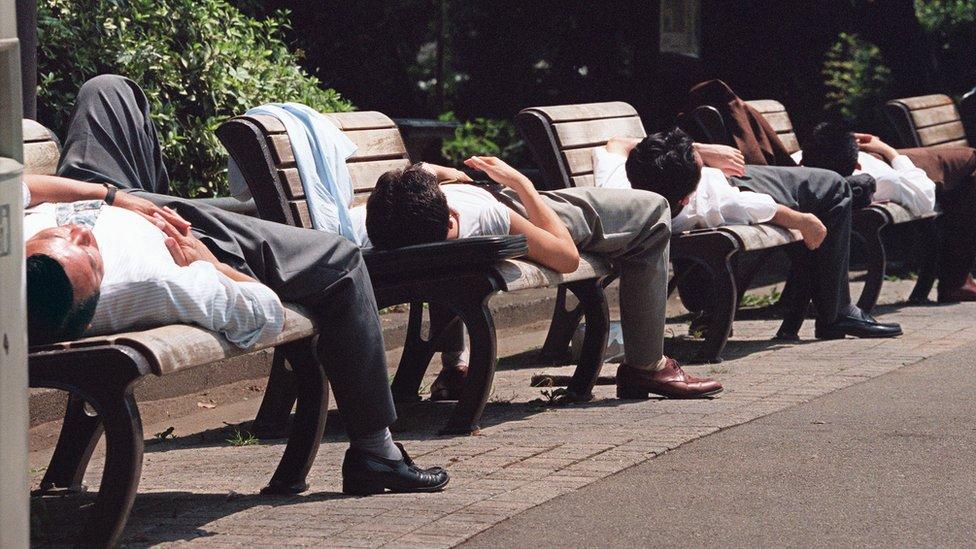 Japonenses tomando el sol en un banco