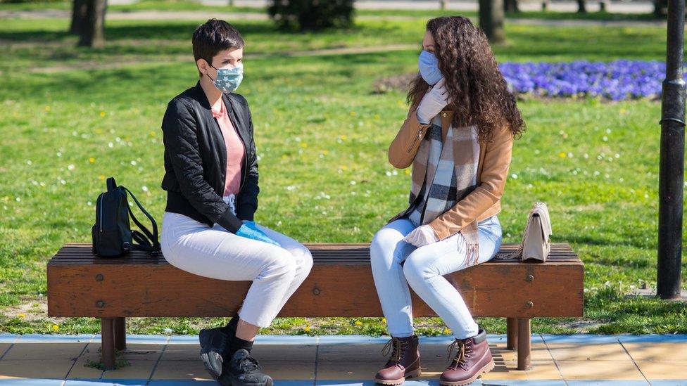 Dos mujeres con mascarilla sentadas en una banca en un parque.