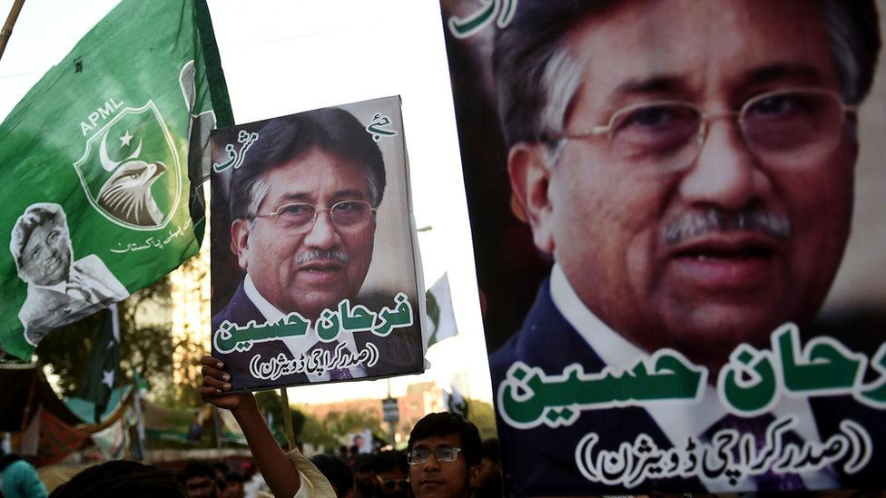 """Demonstrators carry pictures of former military ruler Pervez Musharraf, during a protest following a special court""""s verdict, in Karachi on December 24, 2019."""