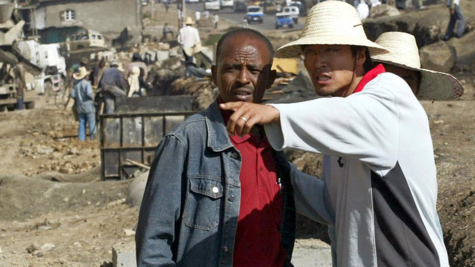 A Chinese construction worker (R) supervises the building of a road in Addis Ababa, 27 April 2007