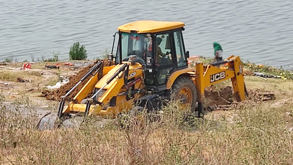 A digger creates a large pit by the banks of the Ganges