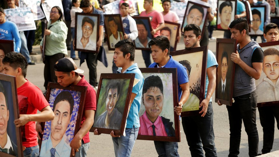 Relatives and activists holding up portraits of the 43 missing students