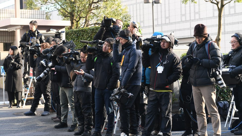 Reporters wait outside the District Court in Tokyo on 8 January