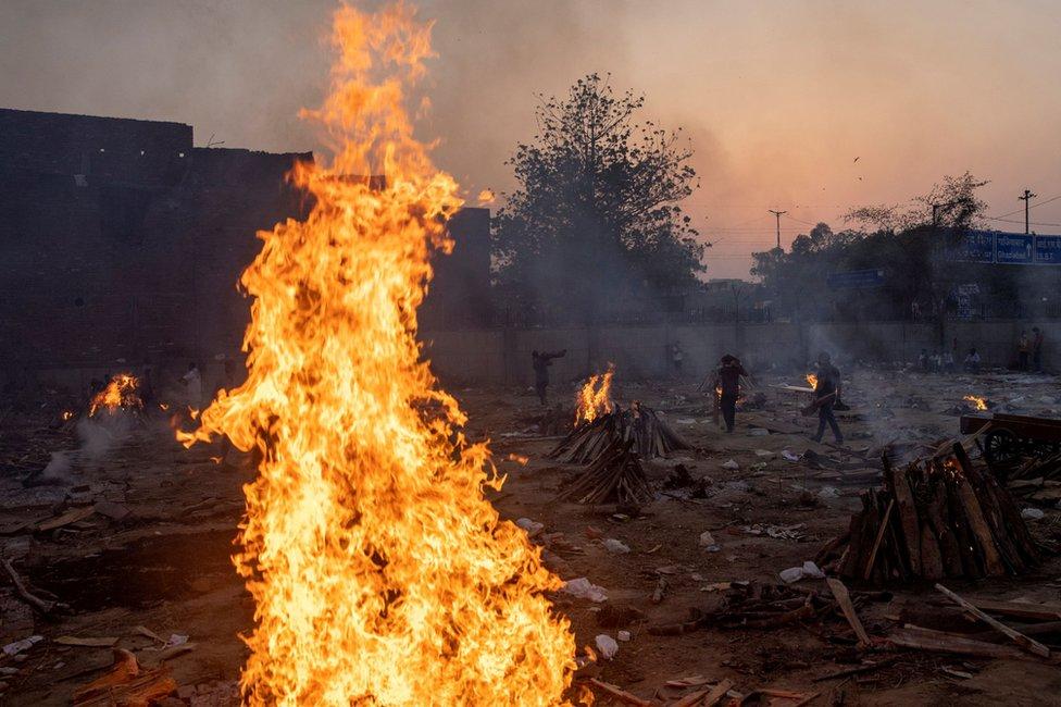 Funeral pyres burn in a crematorium in New Delhi, India