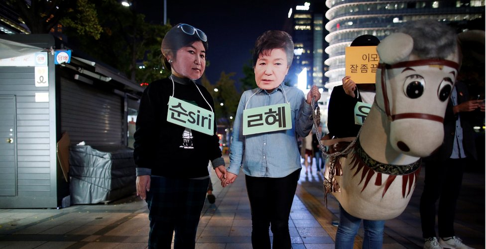 Protesters wearing masks of Choi Soon-sil (left) and President Park Geun-hye (centre), alongside someone dressed as a donkey, at a protest denouncing President Park on 27 October 2016 in Seoul.