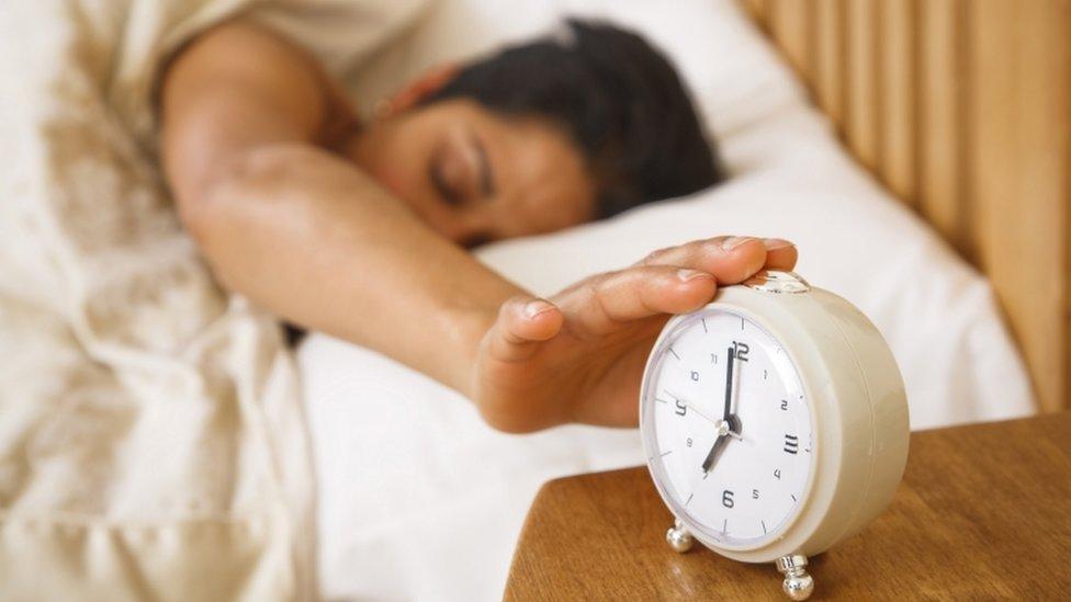 Una mujer apaga la alarma del reloj