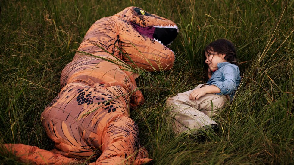 Levi (left) with his cousin Lola (right). Levi picked the T.rex costume for the family photo shoot after finding previous portraits overwhelming