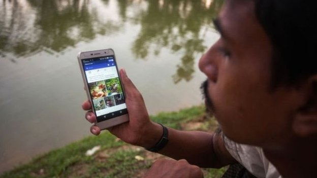 Мешканець країни сидить з телефоном біля озера