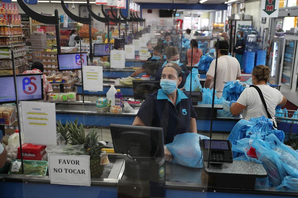 Una empleada en un supermercado en Miami, detrás de láminas de plexiglass