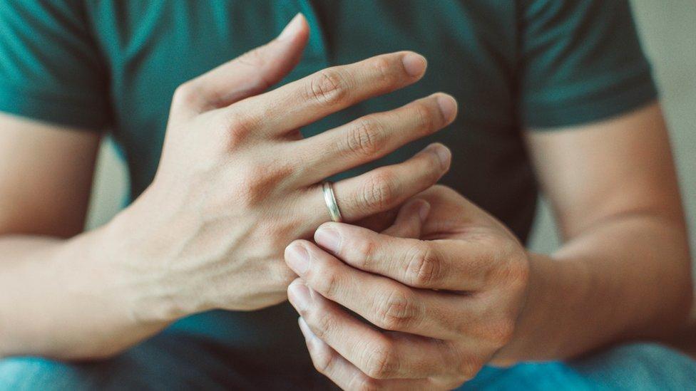 Primer plano de unas manos de hombre con un anillo.