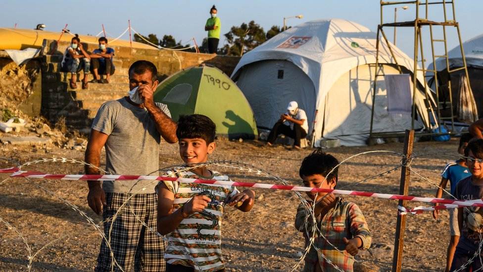Adults and minors refugees and migrants stand behind razor wire at Kara Tepe camp