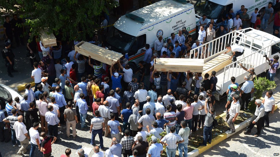 Coffins being carried at the scene of explosion in Suruc, Turkey (20 July 2015)