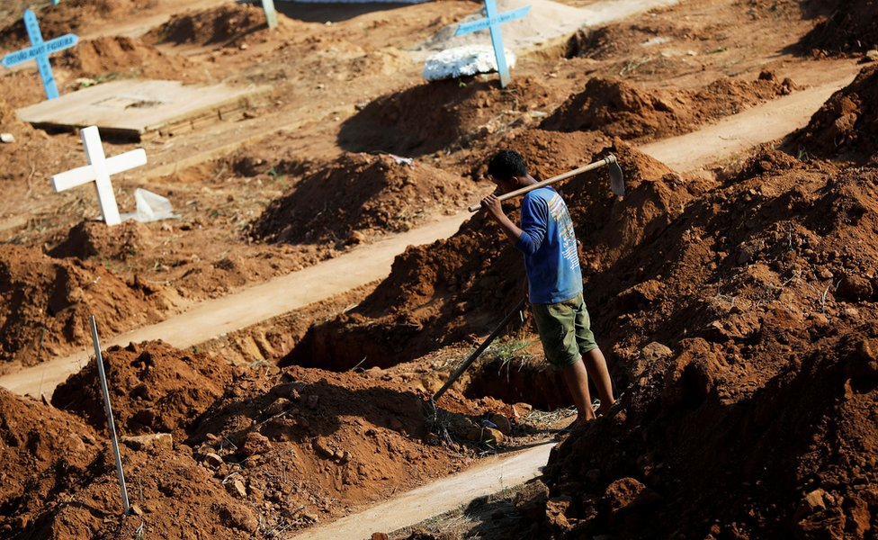 A worker prepares graves at the Sao Sebastiao cemetery in Altamira, Brazil