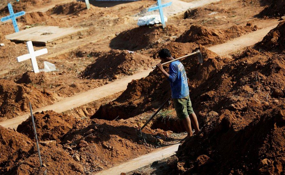A worker prepares graves at the Sao Sebastiao cemetery in Altamira, Brazil