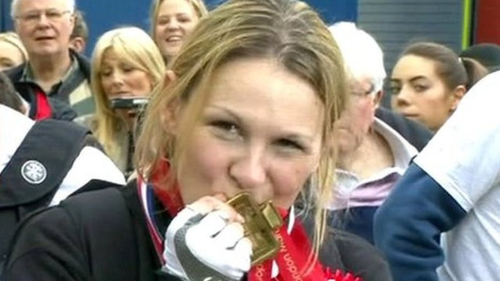 Claire Lomas kisses her medal for completing the London Marathon