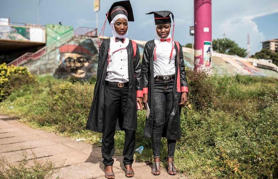 Two young women pose for a portrait, dressed in robes after collecting their Bachelor degrees in Conakry on October 12, 2020.
