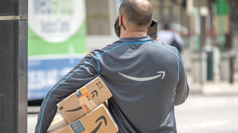 Un trabajador de Amazon, de espaldas, con unos paquetes