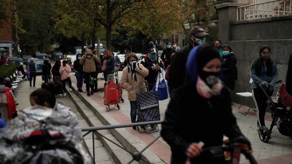 People wait in line to receive food donation in Madrid, Spain on November 04, 2020