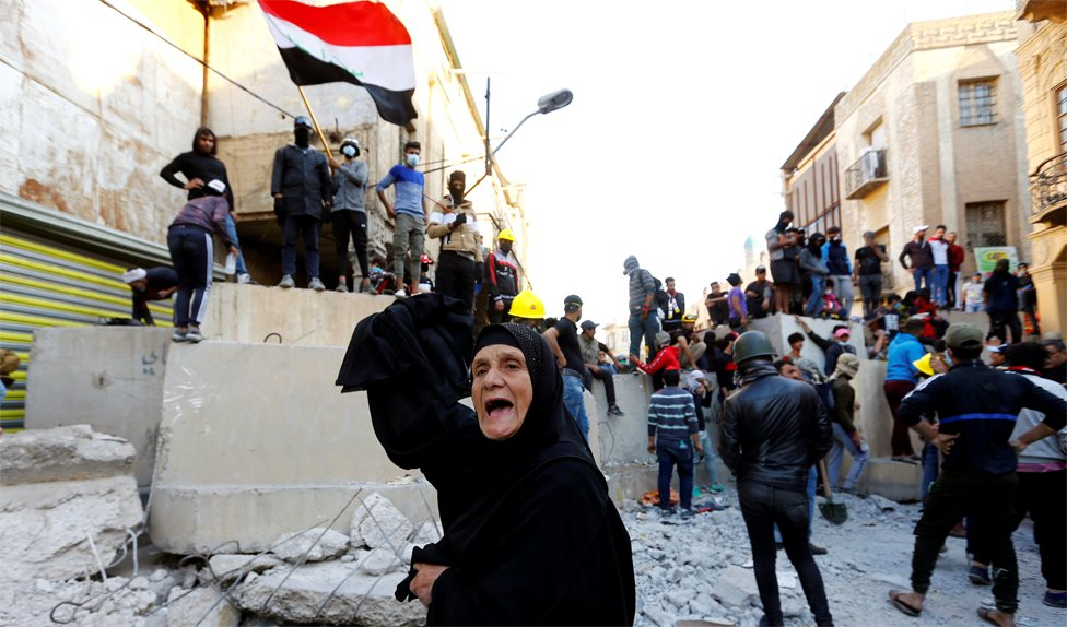 A woman shouts in front of anti-government protesters in Baghdad, Iraq (21 November 2019)