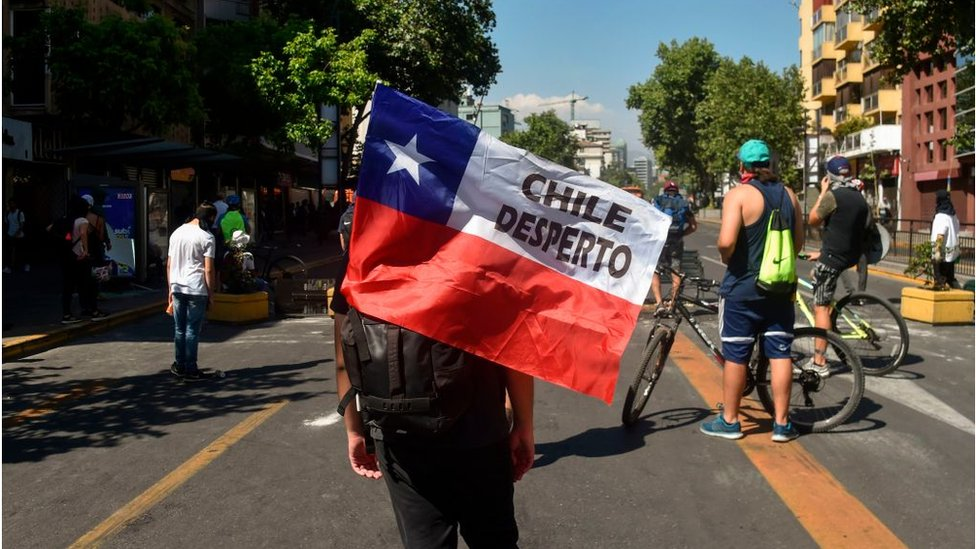 manifestante con bandera chilena que dice chile despertó
