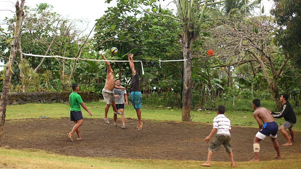 A group of local men and boys play volleyball on a road side court in their village outside of Lotofaga
