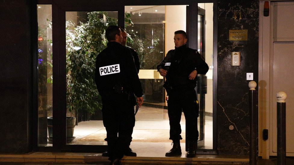 French police officers stand guard at the entrance of the building where British photographer David Hamilton was found dead at his home