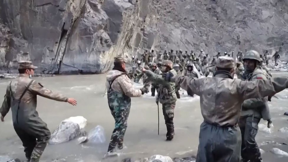 This video frame grab taken from footage recorded in mid-June 2020 and released by China Central Television (CCTV) on February 20, 2021 shows Chinese (foreground) and Indian soldiers (R, background) during an incident where troops from both countries clashed