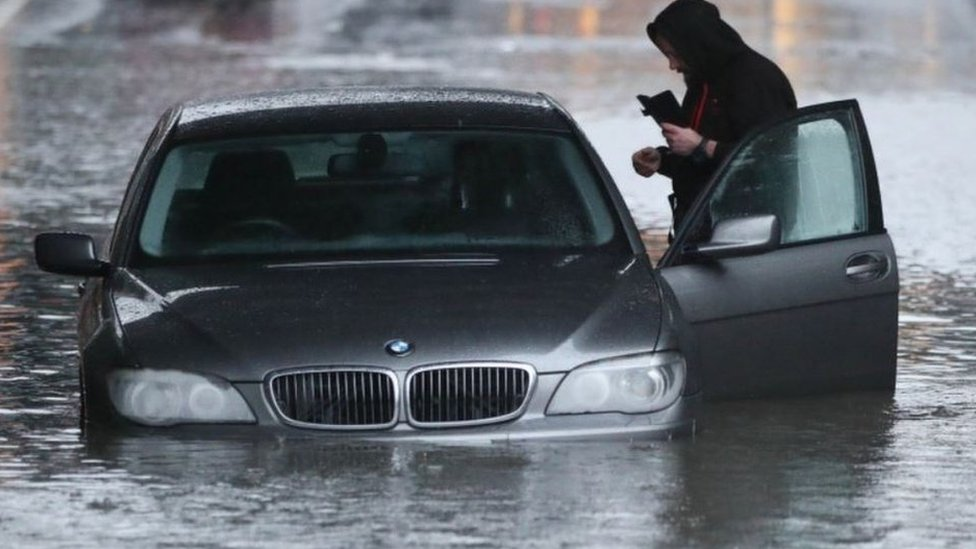 A man with car in a flooded street Sheffield, after torrential rain in the area.