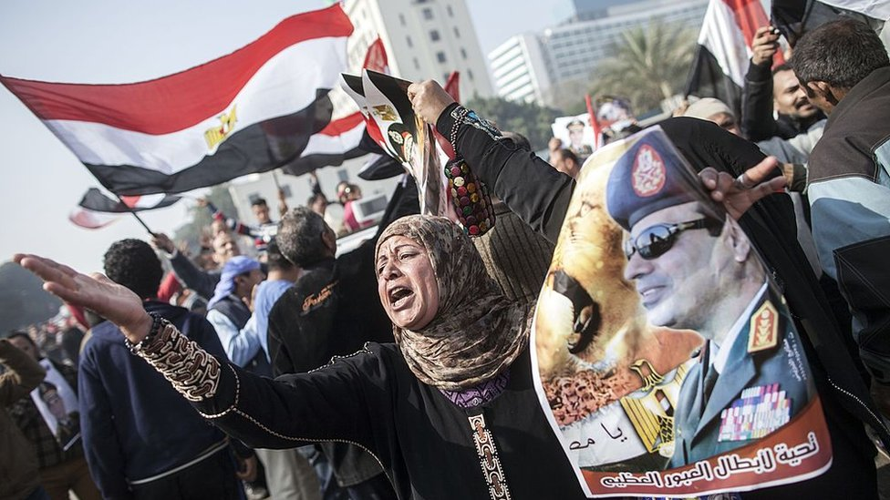 An Egyptian government supporter holds up a poster of Abdul Fattah al-Sisi at a rally in Cairo on the third anniversary of the revolution on 25 January 2014