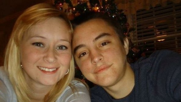 the young couple in front of a xmas tree