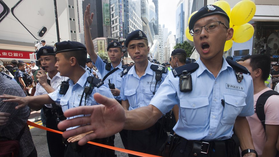 Hong Kong police officers clear a street near the Sogo department store in Causeway Bay before the annual pro-democracy march begins, Causeway Bay, Hong Kong, China, 01 July 2018.