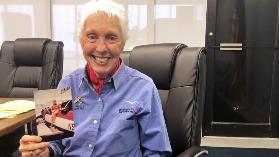 Wally funk holding a photo of herself