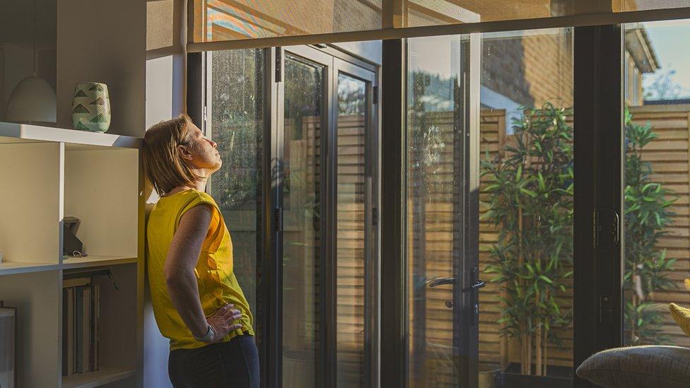 Mulher tomando sol dentro de casa
