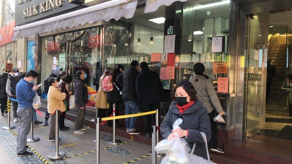 上海部分店家仍正常營業,市民出門皆戴著口罩