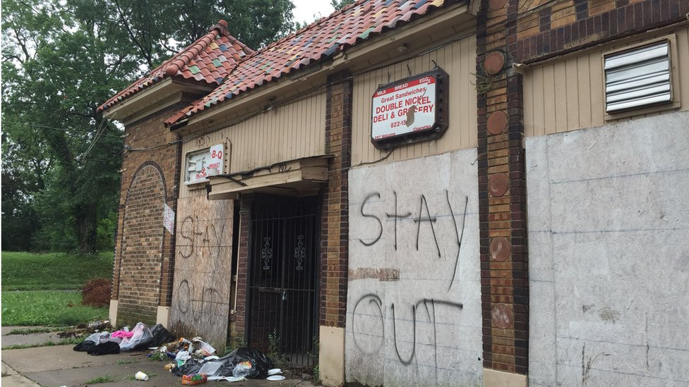 """Boarded up building with piles of rubbish outside, and the words """"Stay Out"""" in spray paint."""