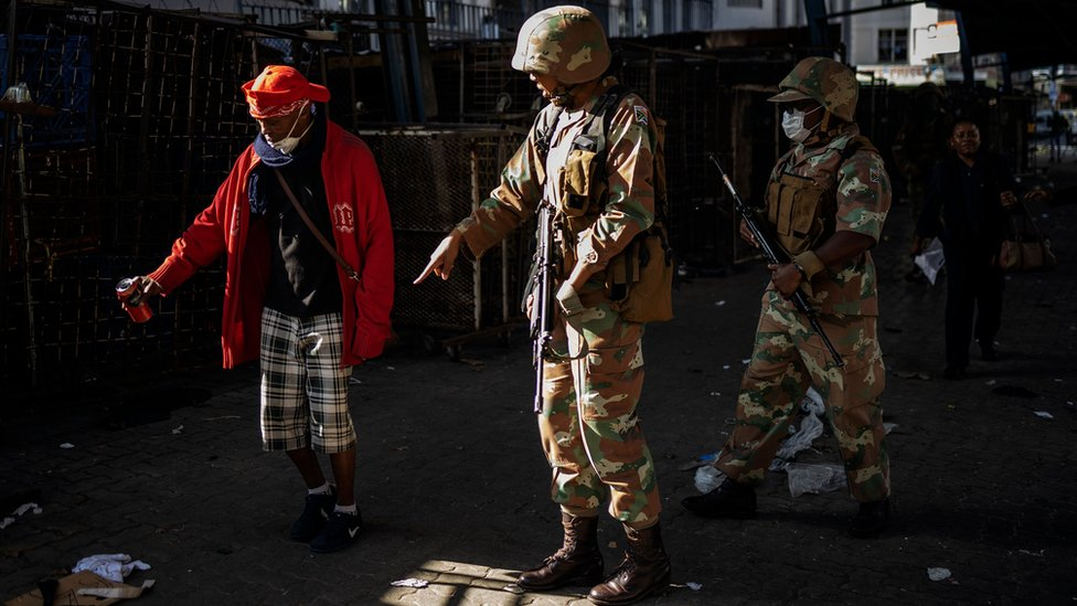 A South African National Defence Force (SANDF) soldier instructs a homeless man to discard his beer on the ground during an operation to enforce a national lockdown in the Johannesburg CBD, on March 27, 2020