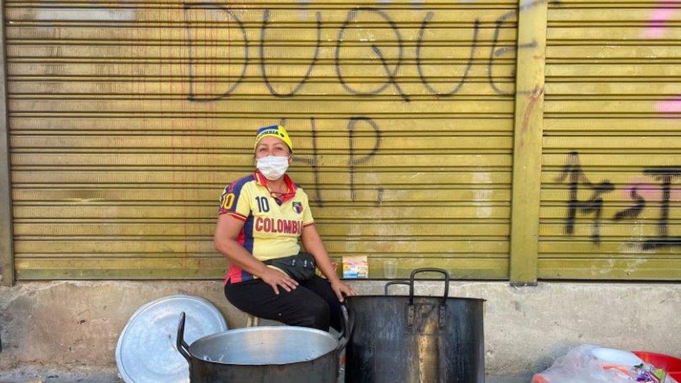 """Una señora en Cali. A sus espaldas una valla pintada con las palabras """"Duque HP""""."""