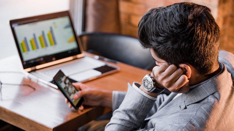 Un hombre procrastinando con su celular.