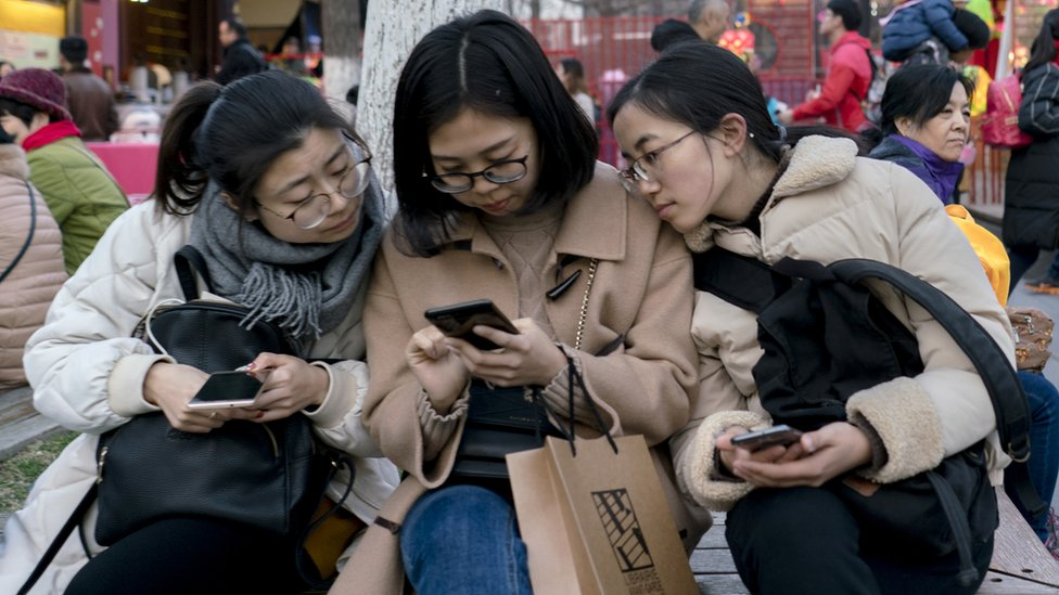 Women look at a phone in a chair on the street.