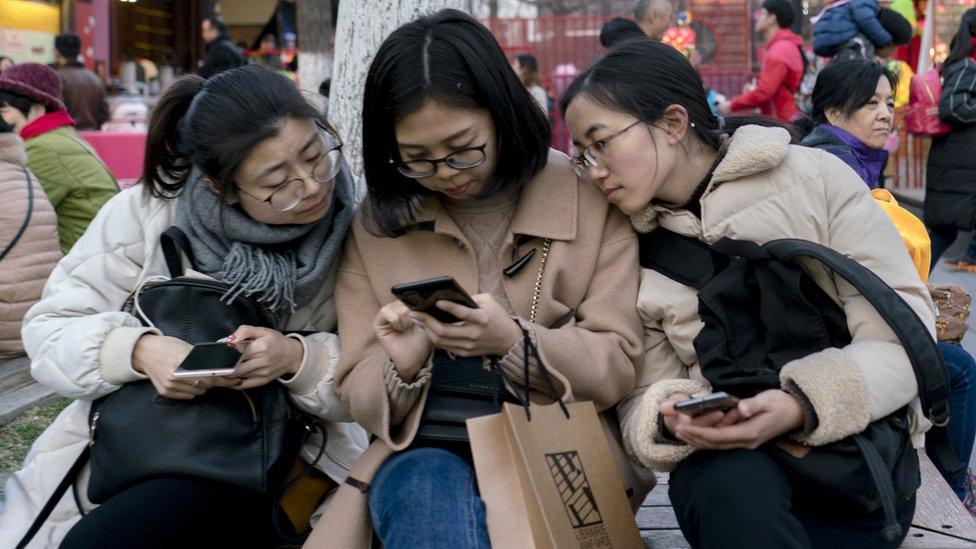 Mujeres mirando un teléfono en una silla en la calle.