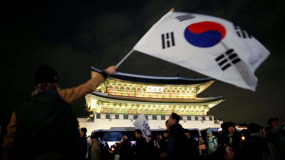 A man waves a national flag as people march toward the Presidential Blue House during a rally demanding President Park Geun-hye to step down
