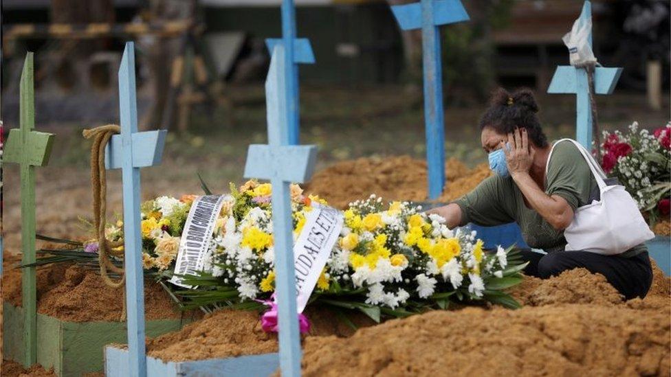 Mulher chora diante de túmulo em Manaus