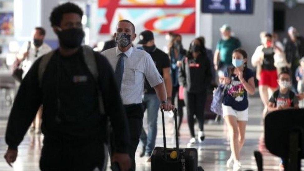 مسافرون يرتدون كمامات في مطار