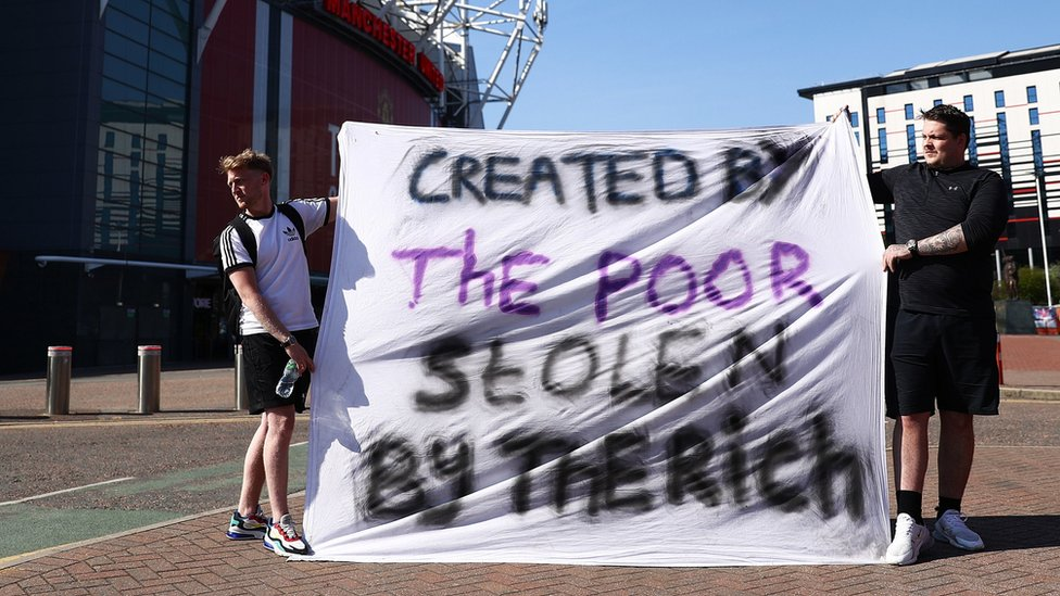 "Fans told a banner reading: ""Created by the poor, stolen by the rich"" outside Old Trafford in Manchester"
